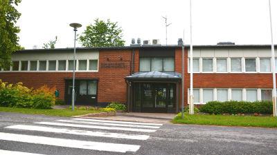 Ett lågt rött tegelhus vid en övergångsväg. På väggen står kunnanvirasto, kommunkansliet.