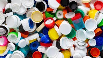 Korkar och andra småsaker i plast på ett ljusblått bord.