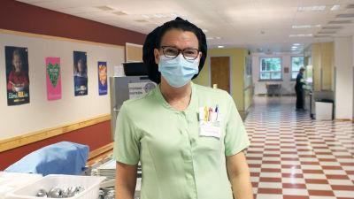 kvinna i munskydd står i skolmatsal