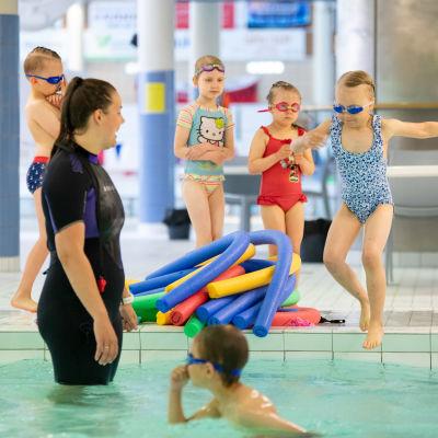 Lapset hyppäävät uima-altaan reunalta veteen uimakoulussa, uimaohjaaja seuraa vieressä.