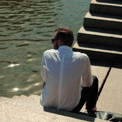 Ensam man sitter vid kajen och tittar ut över vattnet.