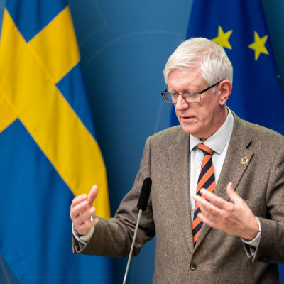 Johan Carlson, generaldirektör på Folkhälsomyndigheten, på pressträff på regeringskansliet framför svenska flaggor.