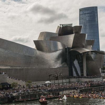 En person gör ett konsthopp från ett tak framför Guggenheim Bilbao.