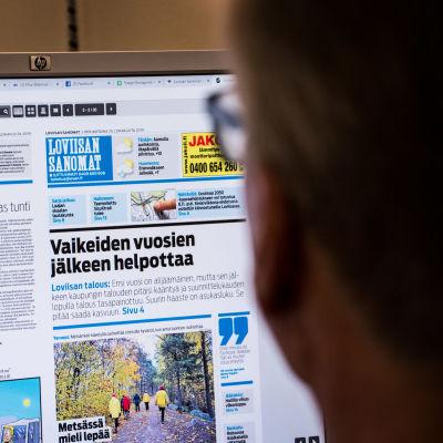 Person läser Loviisan Sanomats nätversion