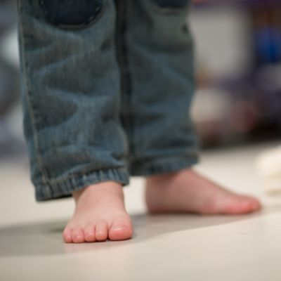 Barfota barnfötter och ett kramdjur på golvet bredvid.