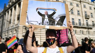 En demonstrant håller upp ett plakat med en bild på premiärminister Viktor Orbán. På bilden har någon redigerat in en regnbågsflagga som Orbán håller i.
