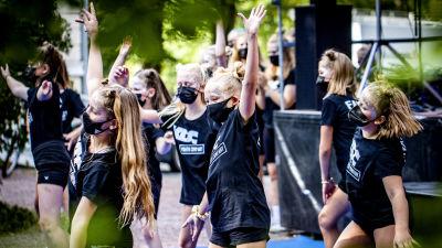 Barn iförda svarta t-skjortor och munskydd dansar.
