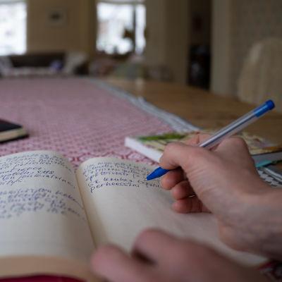 Lähikuva päiväkirjan kirjoittamisesta pöydän ääressä.