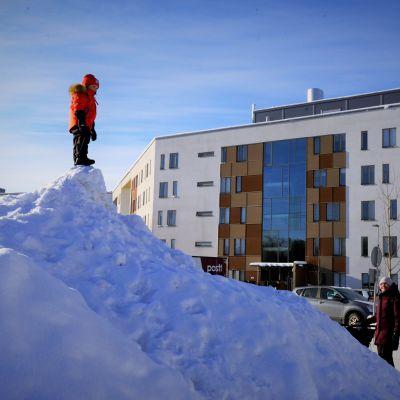 Lapsoi seisoo lumikasan päällä.