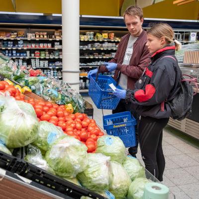 Helsinki-avun vapaaehtoiset Inga Strauss ja Miika Tulkki kaupassa.