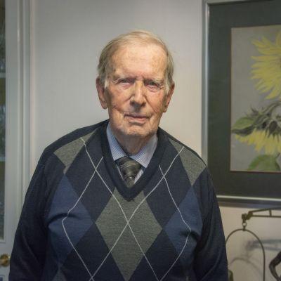 Äldre man med tröja, skjorta och slips framför tavla.