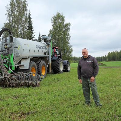 Maanviljelijä Jukka Leikkonen. Taustalla traktori, johon kiinnitetty karjalannan levitin.