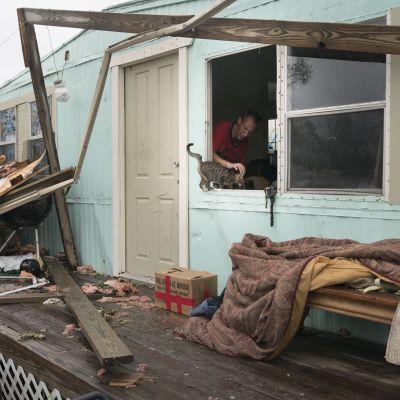 Man och katt vid översvämningsdrabbat hus i Texas.