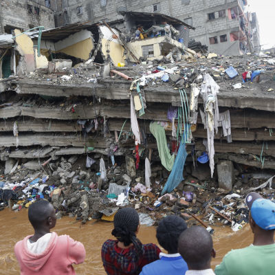 Invånare i slumområdet Mathare i Nairobi står och tittar på det kollapsade huset.