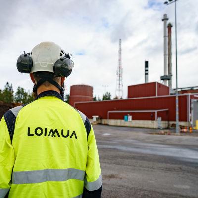 Vanajan hakevoimala Hämeenlinnassa. Etualalla työntekijä selin, keltaisessa liivissä on Loimuan logoteksti.