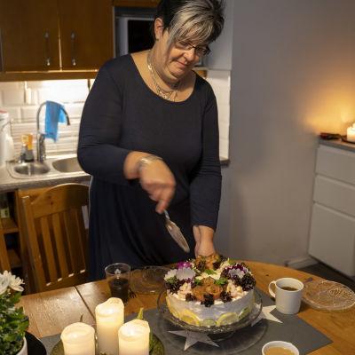 Regina Rehn skär upp en smörgåstårta.
