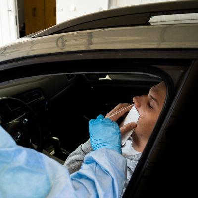 En person sitter i sin bil medan hon testas för covid-19.
