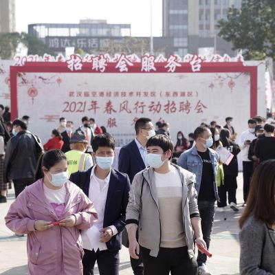 Ihmisiä kävelee Wuhanin kaupungissa kadulla.
