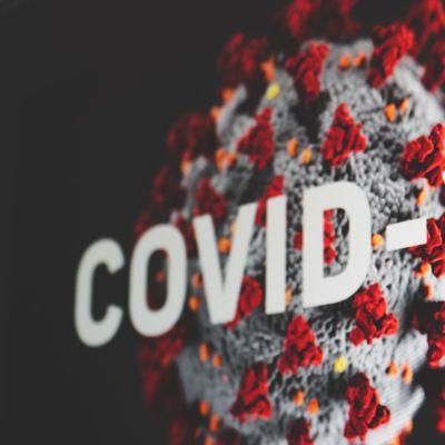 """En coronaviruscell med texten """"Covid-19"""" ovanpå"""