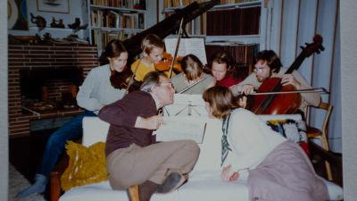En familj sitter tätt runt en soffa och ett piano. En äldre man och kvinna sitter i soffan och fem barn sitter bakom soffan och spelar varsitt instrument i famnen.