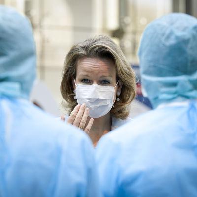 Belgiens drottning Mathilde besöker ett sjukhus i Liege på fredagen. Hon har en skyddsmask för ansiktet. I förgrunden ser man två vårdare i full skyddsutrustning.