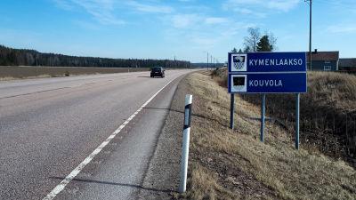 En blå trafikskylt bredvid en större väg.