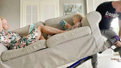 Carro ligger i soffan med sin dotter som läser bok. Carros man lyfter soffan så halva är i luften medan han dammsuger under soffan.