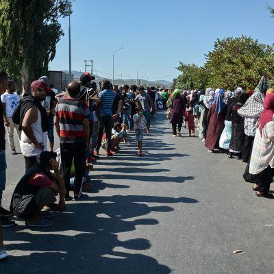 Tusentals flyktingar och migranter har slagit läger vid en landsväg på Lesbos, i stället för att flytta in i ett nytt, tillfälligt läger.