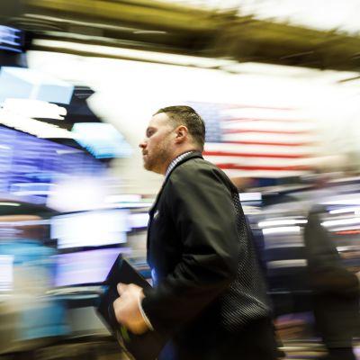 Meklari juoksee New Yorkin pörssissä. Taustalla Yhdysvaltain lippu.