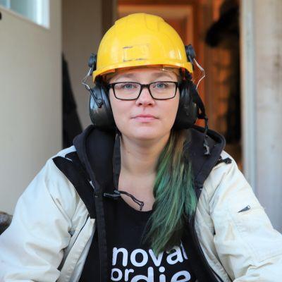 Nainen istuu talon portailla työmaakypärä päässään.