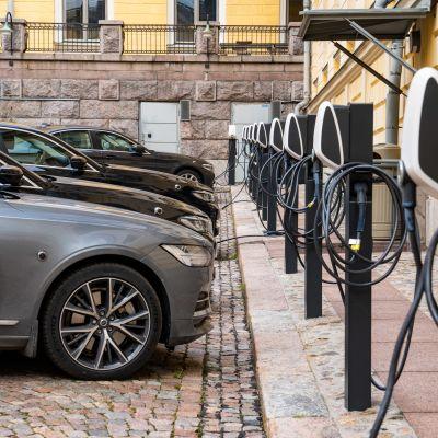 Hybridbilar står i rad vid en stenvägg och laddas på Statsrådets innergård.