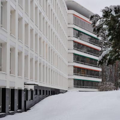 Paimion parantola kuvattuna helmikuussa illansuussa. Lunta on runsaasti, ikkunoiden yläpuolella oranssit ja vihreät markiisit.