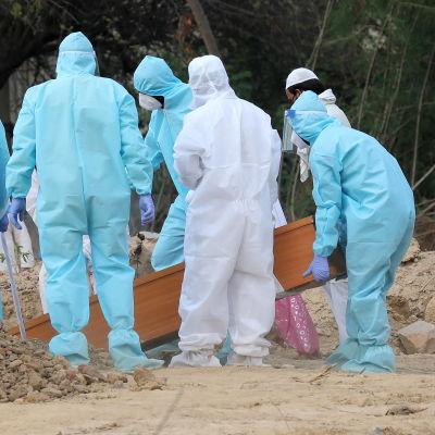 De anhöriga var klädda i skyddsdräkter vid en begravning i New Delhi på fredagen. Coviddöda begravs på en särskild begravningsplats.