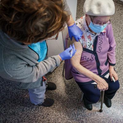Sairaanhoitaja pistää koronarokotteen vanhuksen käsivarteen.