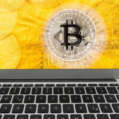Kuvassa kannettavan tietokoneen näytössä on kuva kultaisesta bitcoinista.