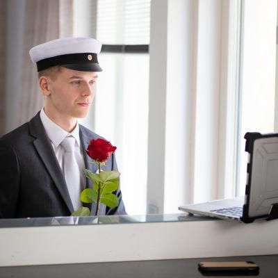 Frans Salminen seisoo ylioppilaslakki päässä tietokoneen ääressä.