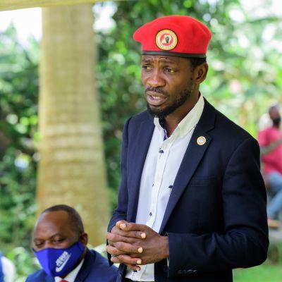 Bobi Wine puhuu tiedotustilaisuudessa ulkotilassa. Hänellä on tumma puku, vaalea kauluspaita ja päässään punainen baretti.