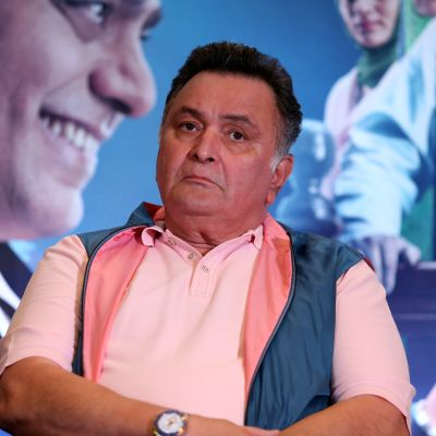 Rishi Kapoor elokuvajulisteen edessä.
