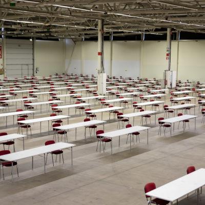Turun yliopiston valintakokeita varten järjestetyt pöydät ja tuolit Turun messukeskuksessa.