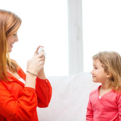 En mamma tar en bild av sin dotter med en kamera