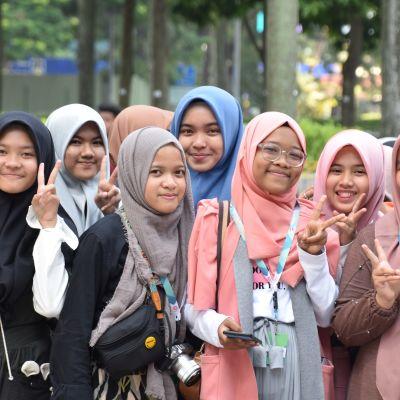 En grupp muslimska flickor i Malaysia poserar för kameran och gör segertecken med fingrarna.