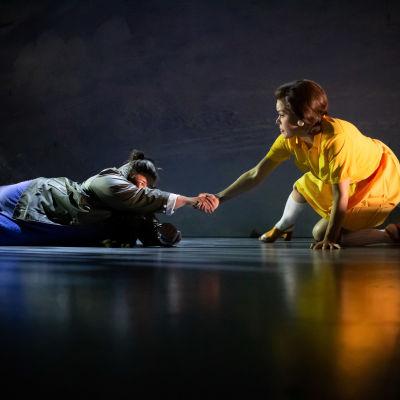 En kvinna i gul klänning sitter på huk på en teaterscen och drar upp en kvinna i grön jacka ur en isvak