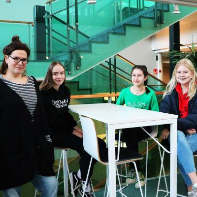 Fyra glada personer står och sitter vid ett bord.