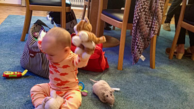 En baby sitter på gilvet och leker med godsedjur.