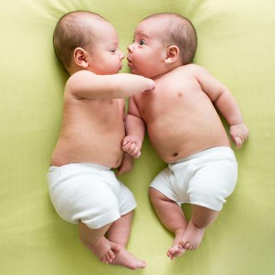 Två bebisar i blöjor ligger och tittar på varandra på en filt.
