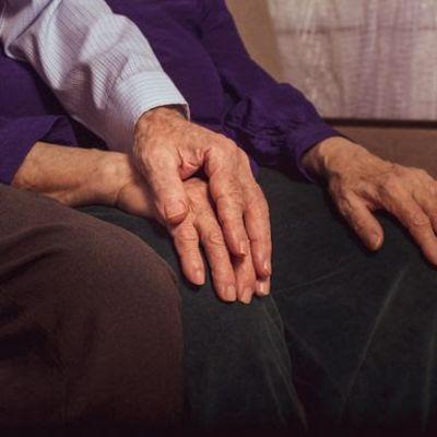 Hoitaja ja hoidettava käsi kädessä.