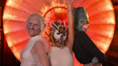 Tre kvinnor i fantastiska djurmasker poserar framför kameran.