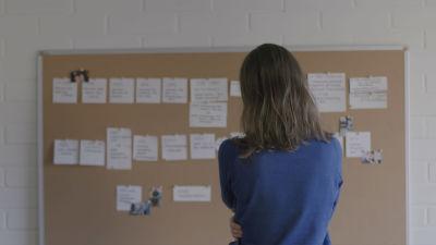 Matilda står med ryggen vänd mot kameran och stirrar på en tavla full av upphängda papperslappar.