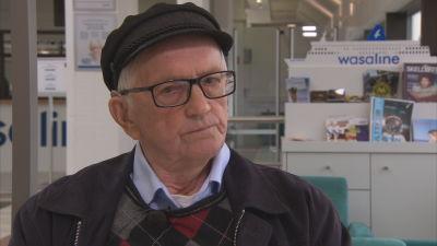 En man med keps och glasögon sitter med en reklam för Wasalines bakom sig.