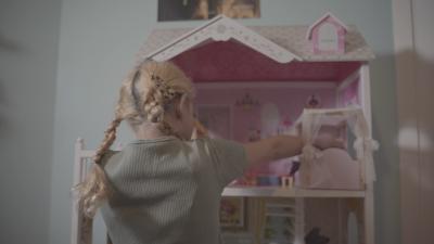 Ett barn tittar på ett dockskåp.